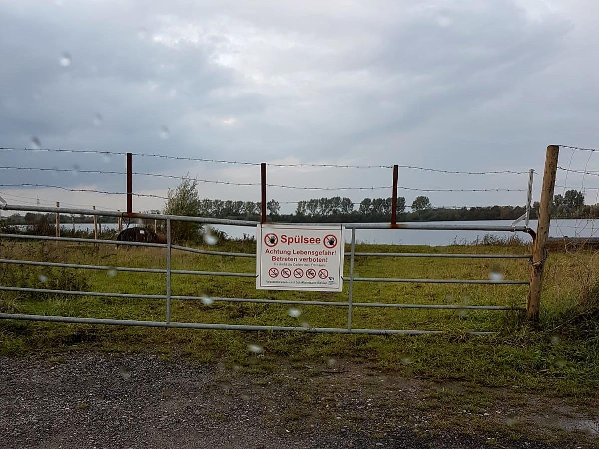 Zaun vor See mit Warnschild Aufschrift Spülsee Lebensgefahr